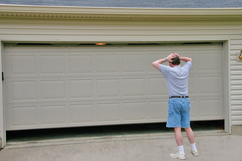 Confused homeowner standing by garage door with hands on his head