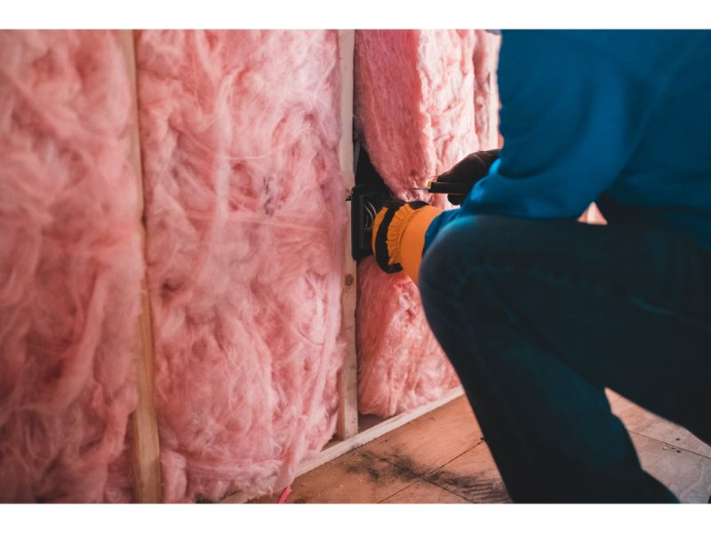 Service technician reaching gloved hand into exposed pink insulation inside wall of garage under construction.