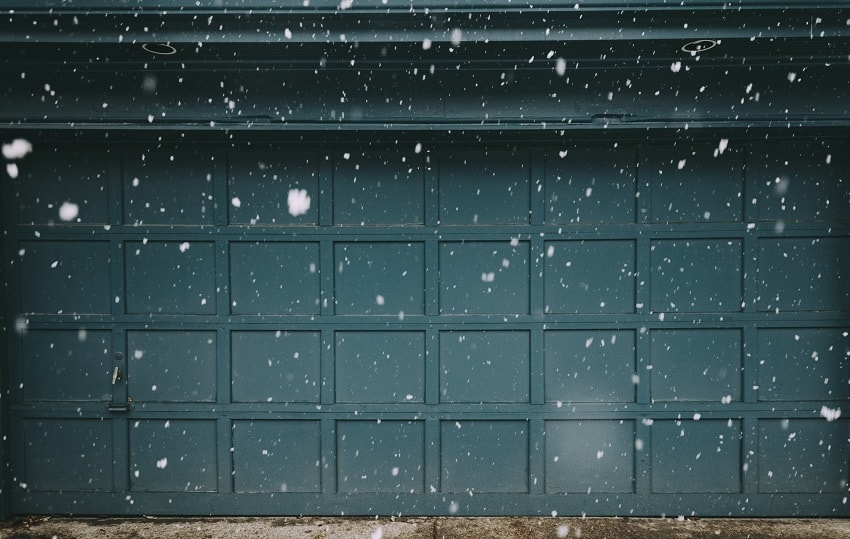 Dark teal paneled two-car garage door through flakes of falling snow in winter season