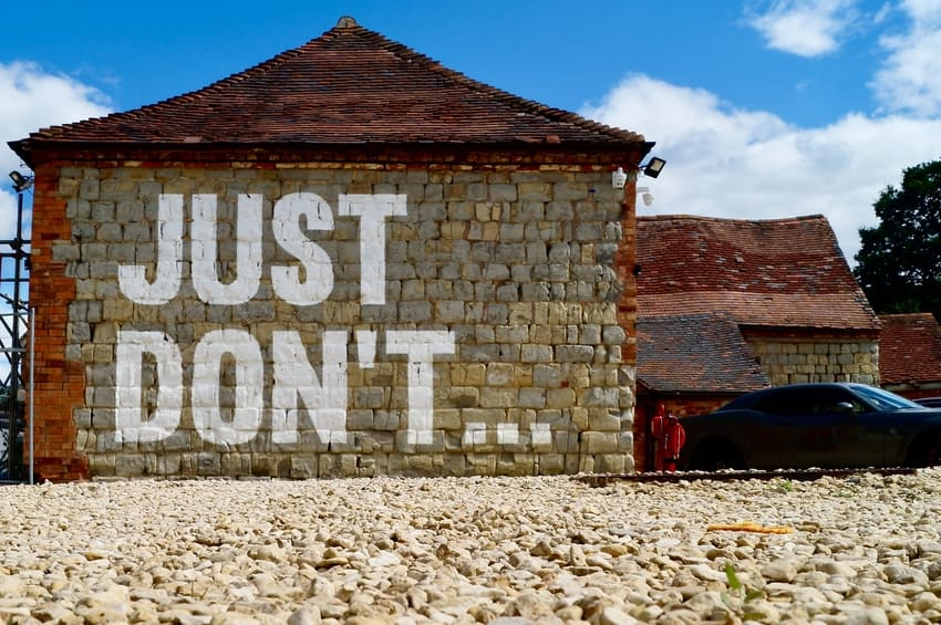 Brick Garage Exterior Painted with Warning Message 'Just Don't...'