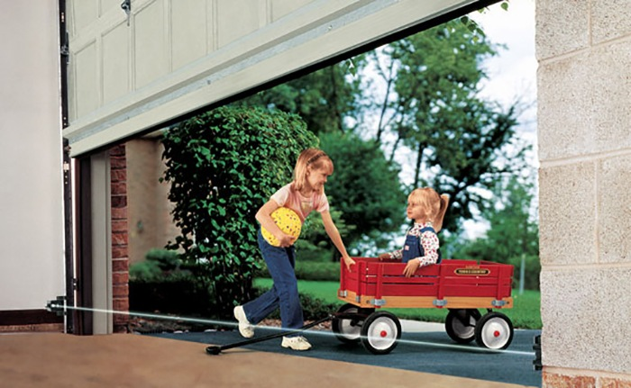 Smiling Girl Pulling Brother in Red Wagon Beneath Partially Open Garage Door into Open Space in Residential Garage