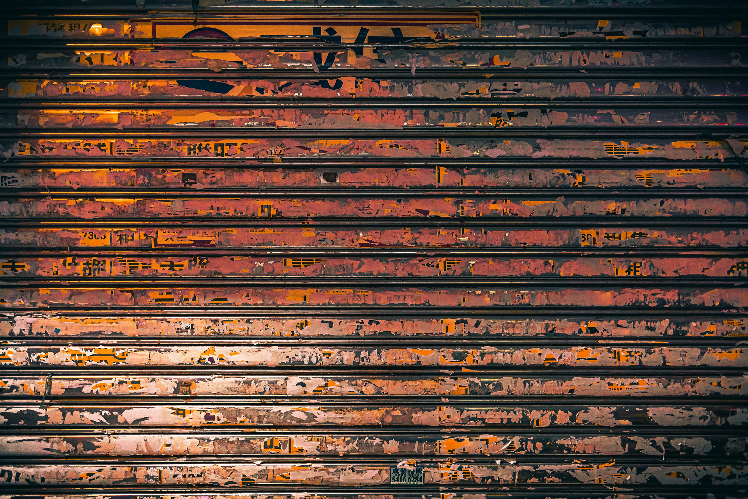 Paneled two-car metal garage door covered in rust