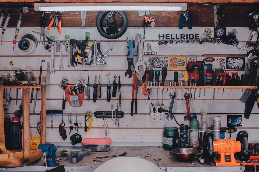 Wrenches, screwdrivers, pliers and other repair tools on wall and shelf of garage workshop